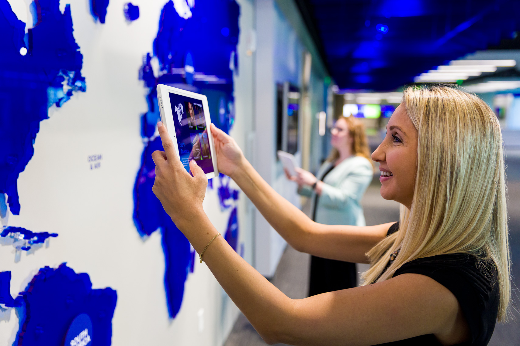 Two women interact with a technology wall and tablets