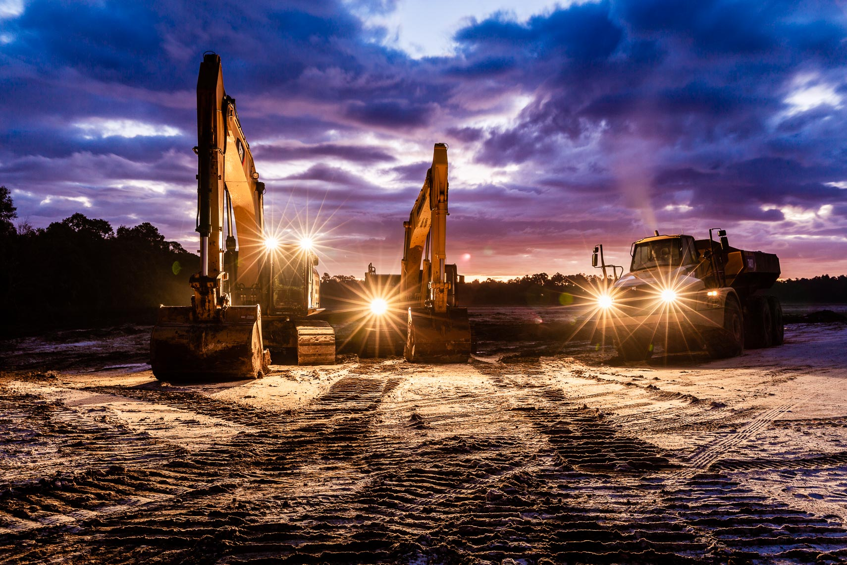 Excavators and Dump Trucks at Sunrise