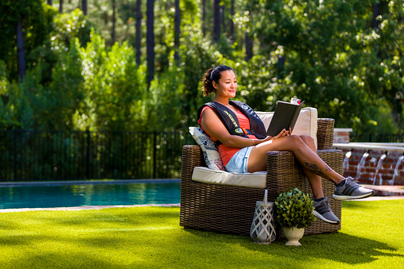 A woman reading a book in her back yard.