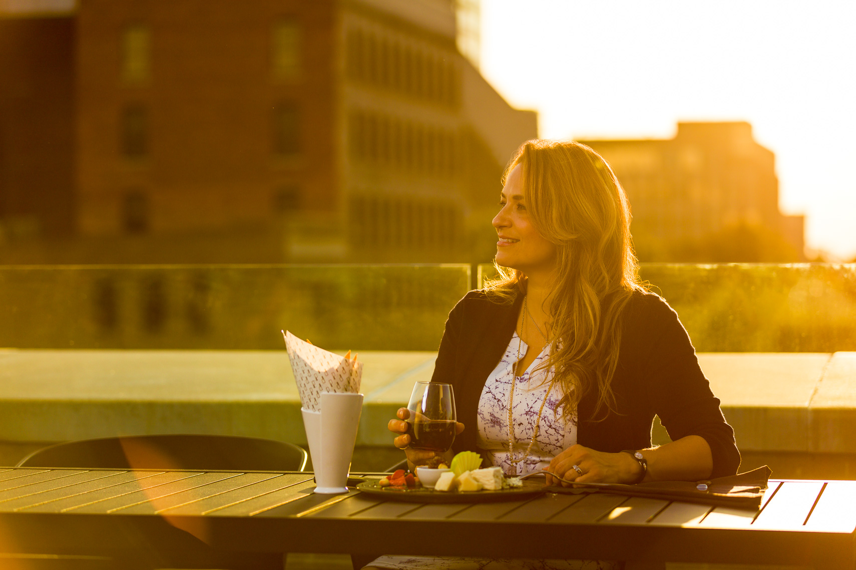 A woman dining and drinking on a rooftop restaurant in downtown Jacksonville Florida