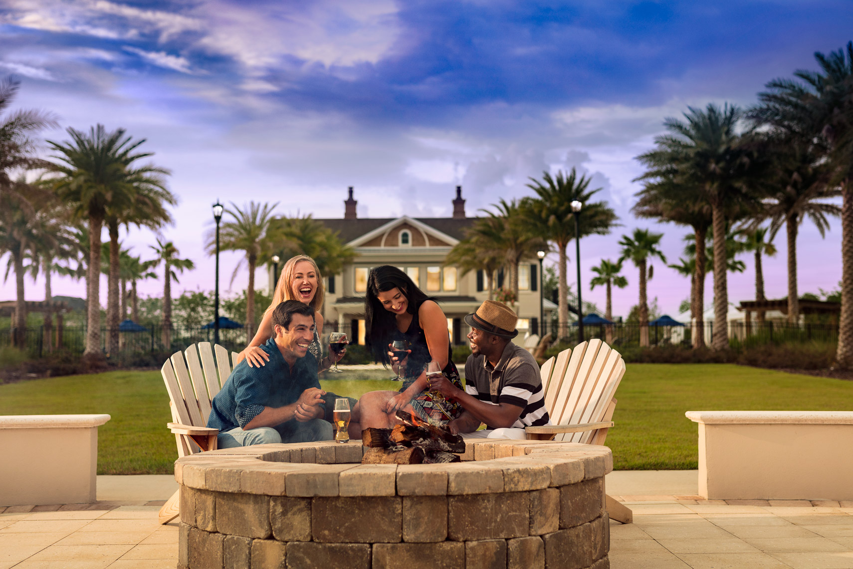 Two couples enjoy drinks together by the fire pit