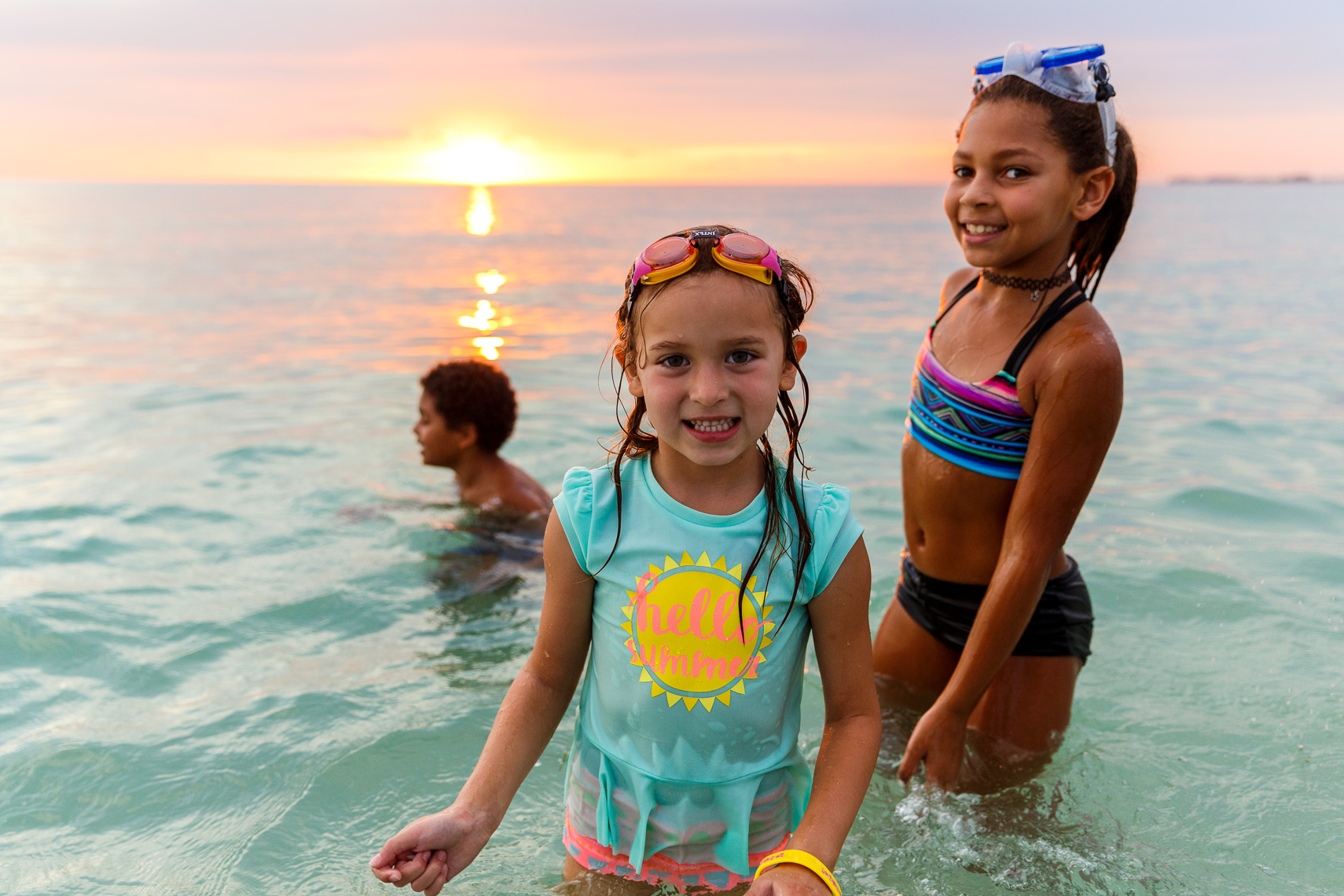 Children play in the Gulf of Mexico at sunset