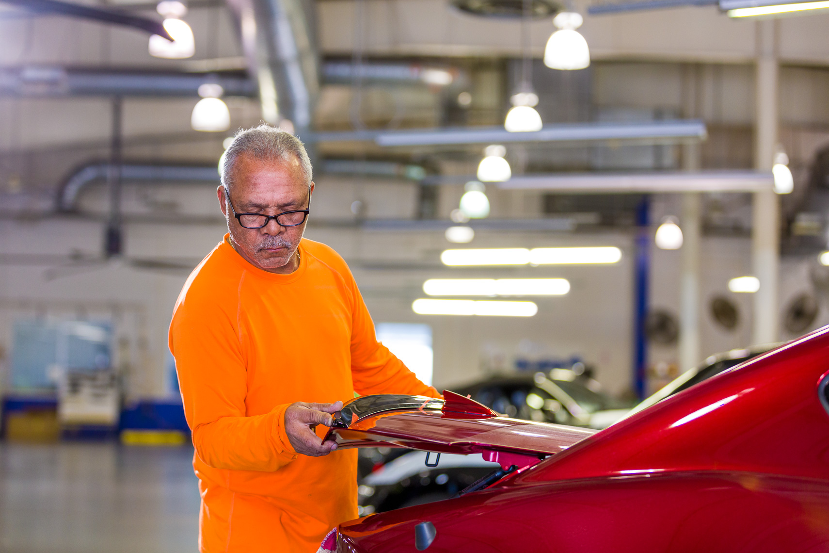 An industrial worker finishes automotive details before the product gets delivered