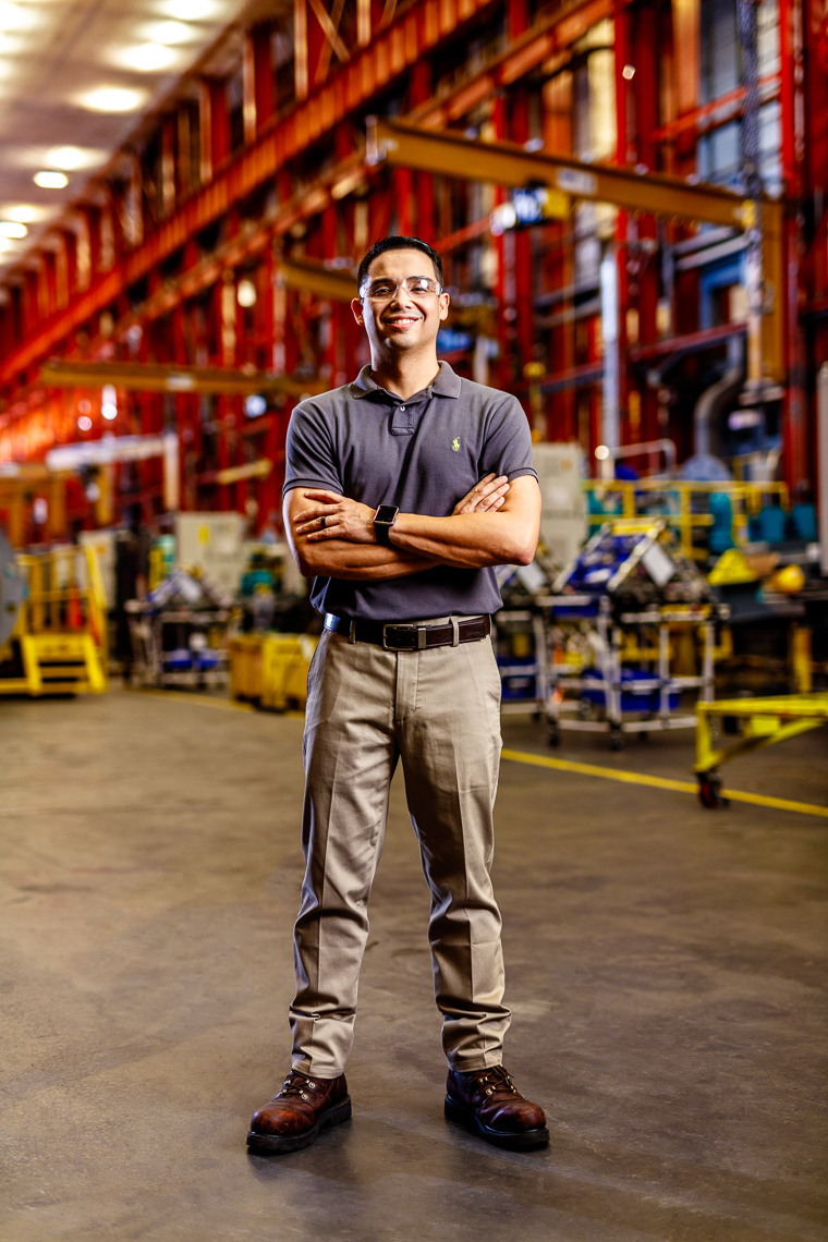 Portrait of an employee at a tech company in an inustrial warehouse